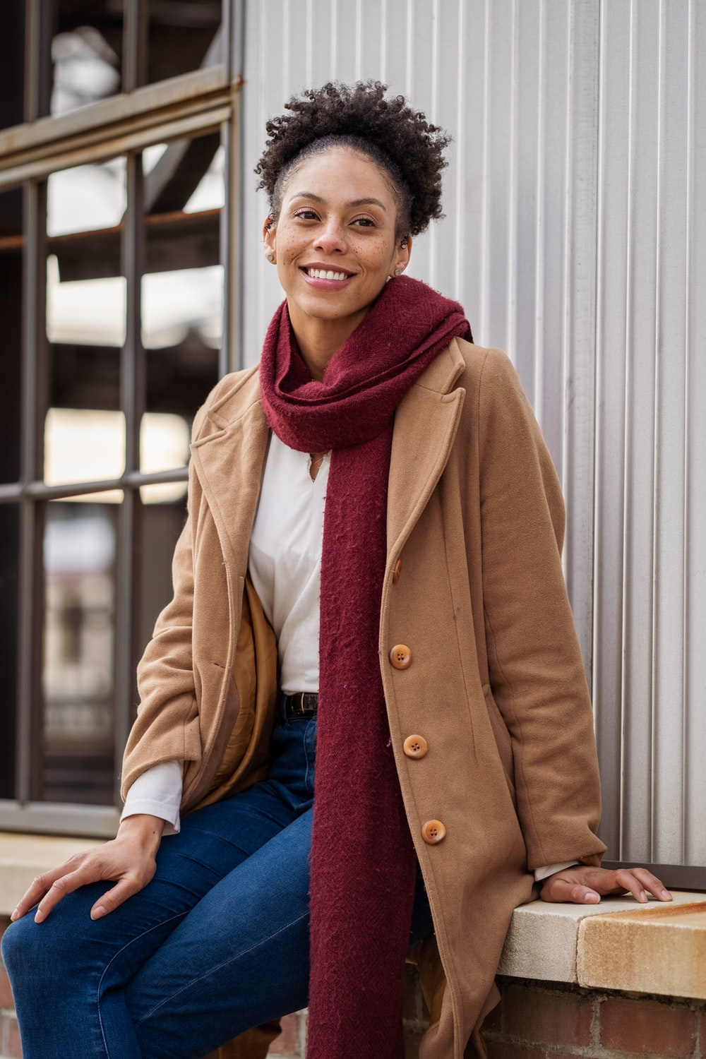 smiling woman in brown coat and blue denim jeans sitting on white wooden bench
