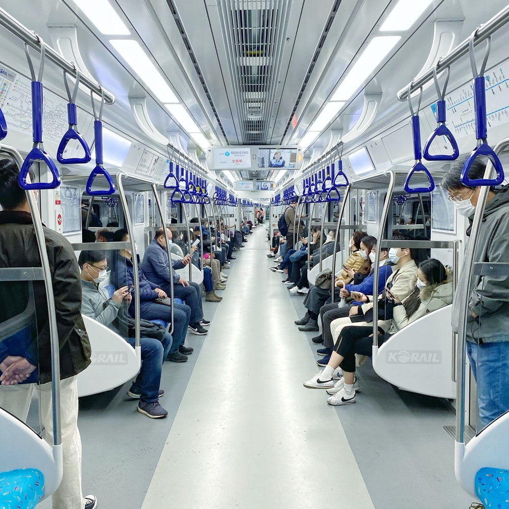 people sitting on blue and white bus seats