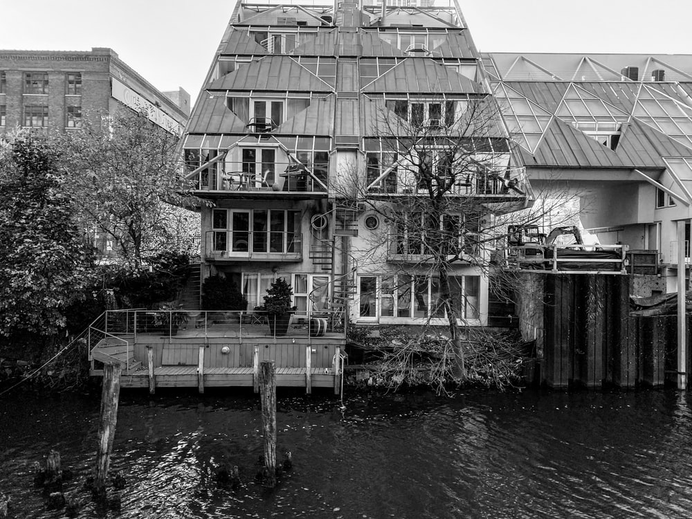 grayscale photo of a building near a river