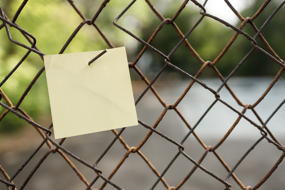 yellow sticky note on gray metal fence