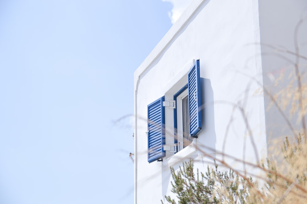 white concrete building with blue window