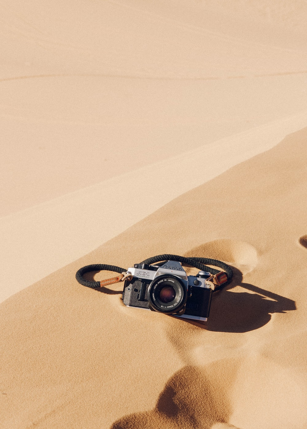 black and silver dslr camera on brown sand