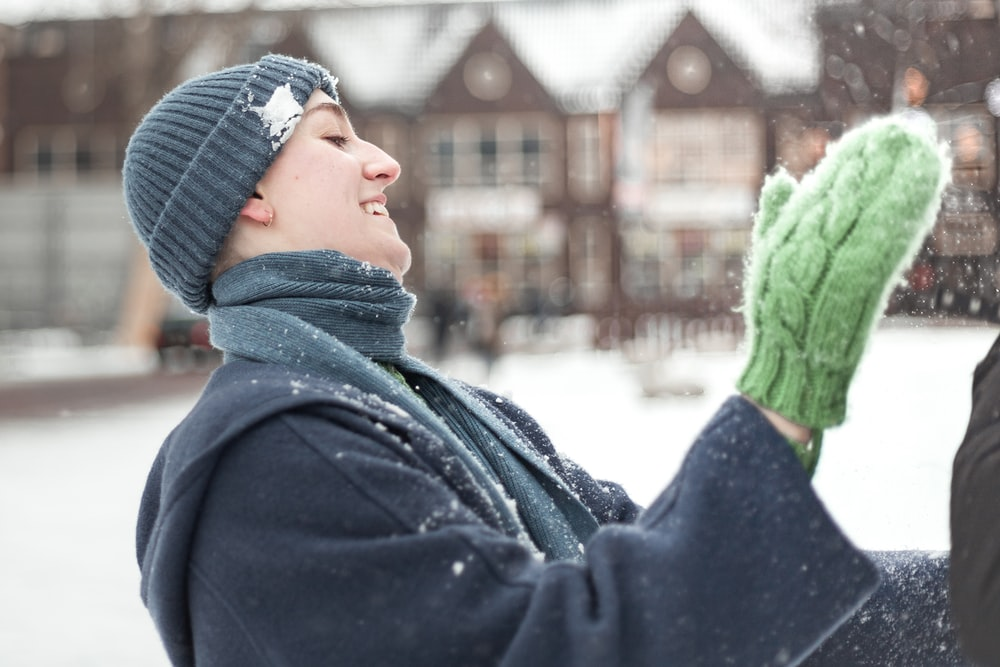 woman in black coat and green knit scarf