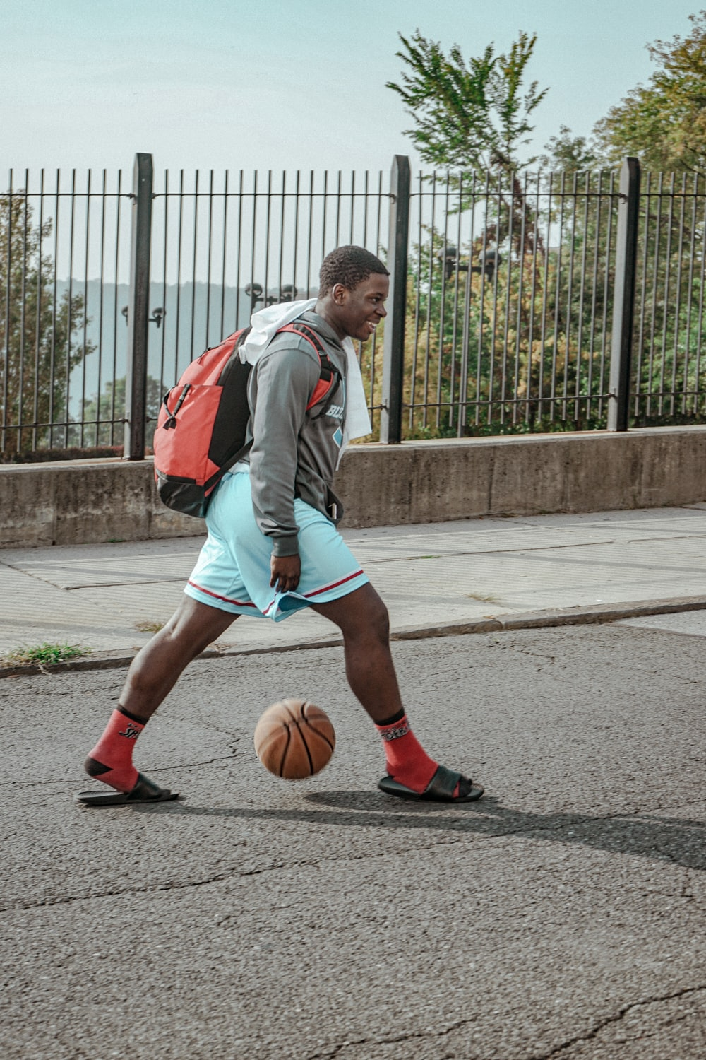 man in green and white nike jersey shirt and red shorts running on gray concrete road