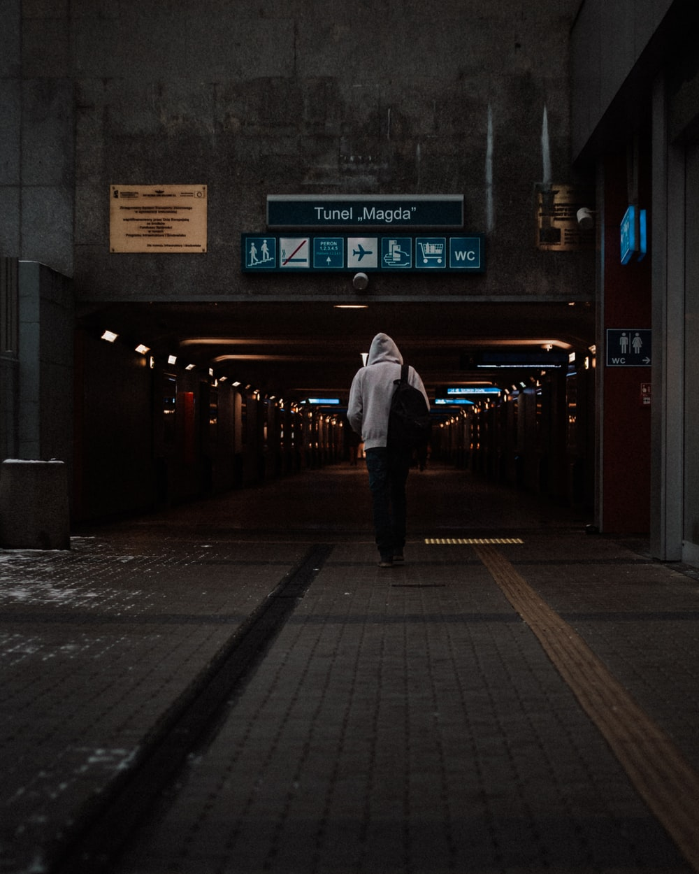 man in white dress shirt and black pants standing on sidewalk during night time