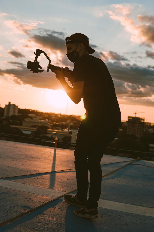 man in black jacket holding black camera during sunset