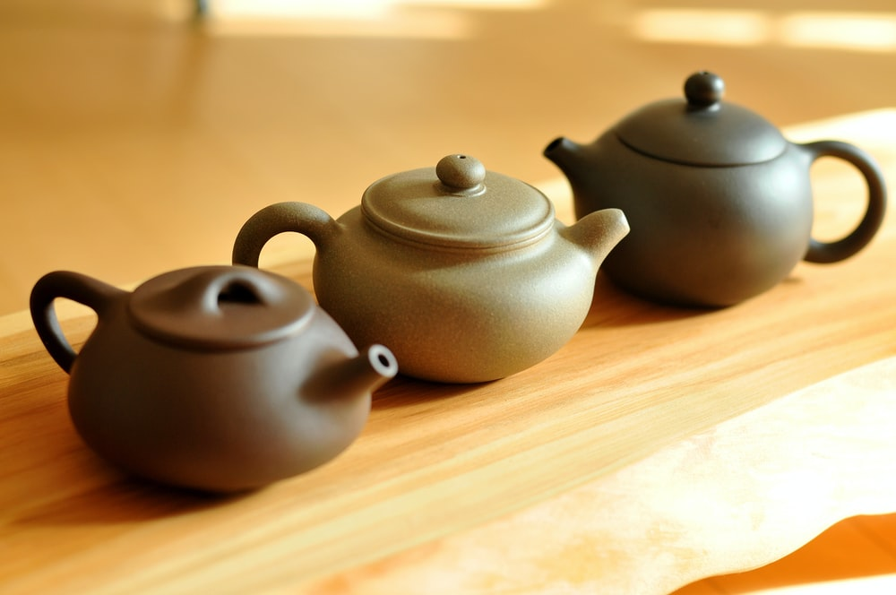 black ceramic teapot on brown wooden table