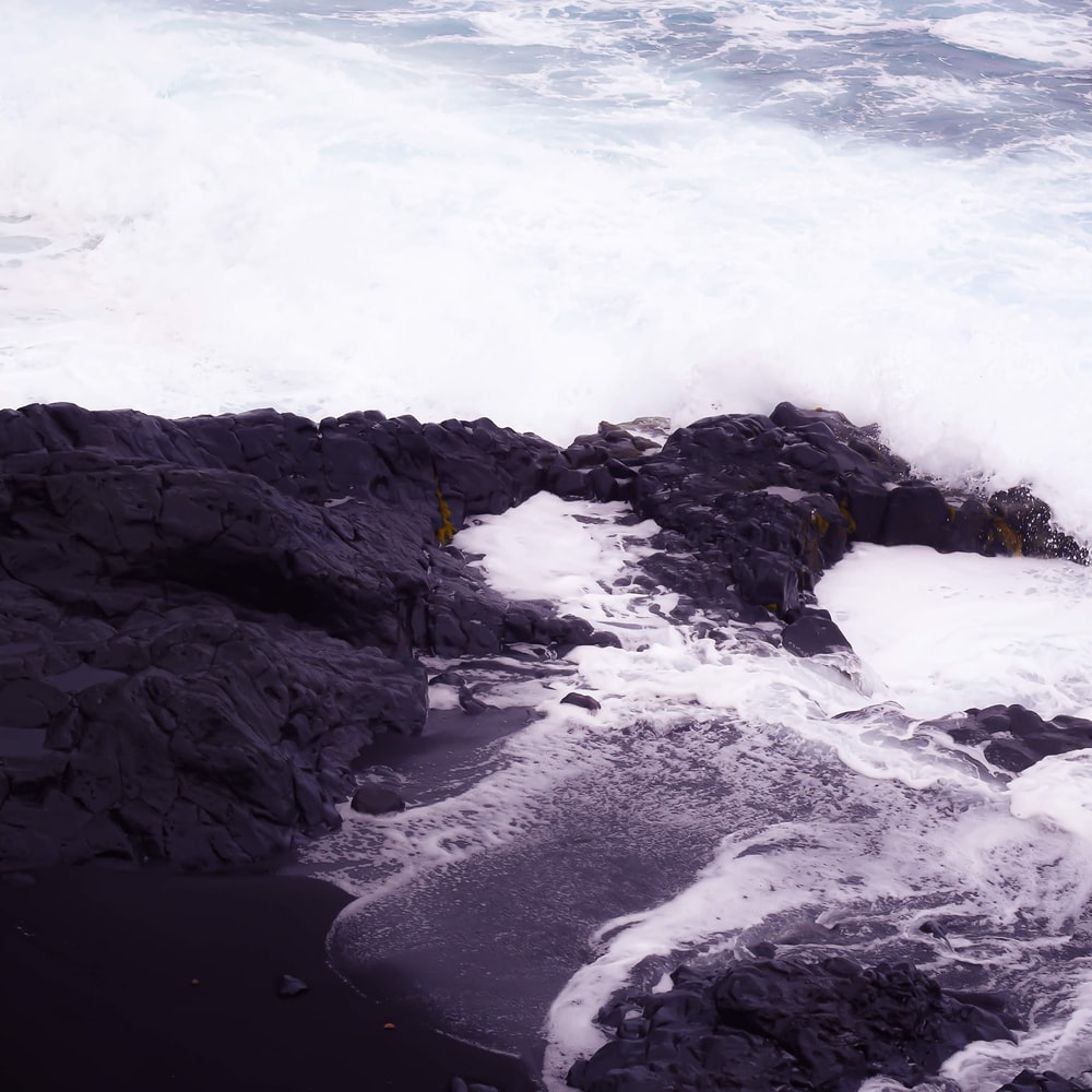 black rock formation on sea water during daytime