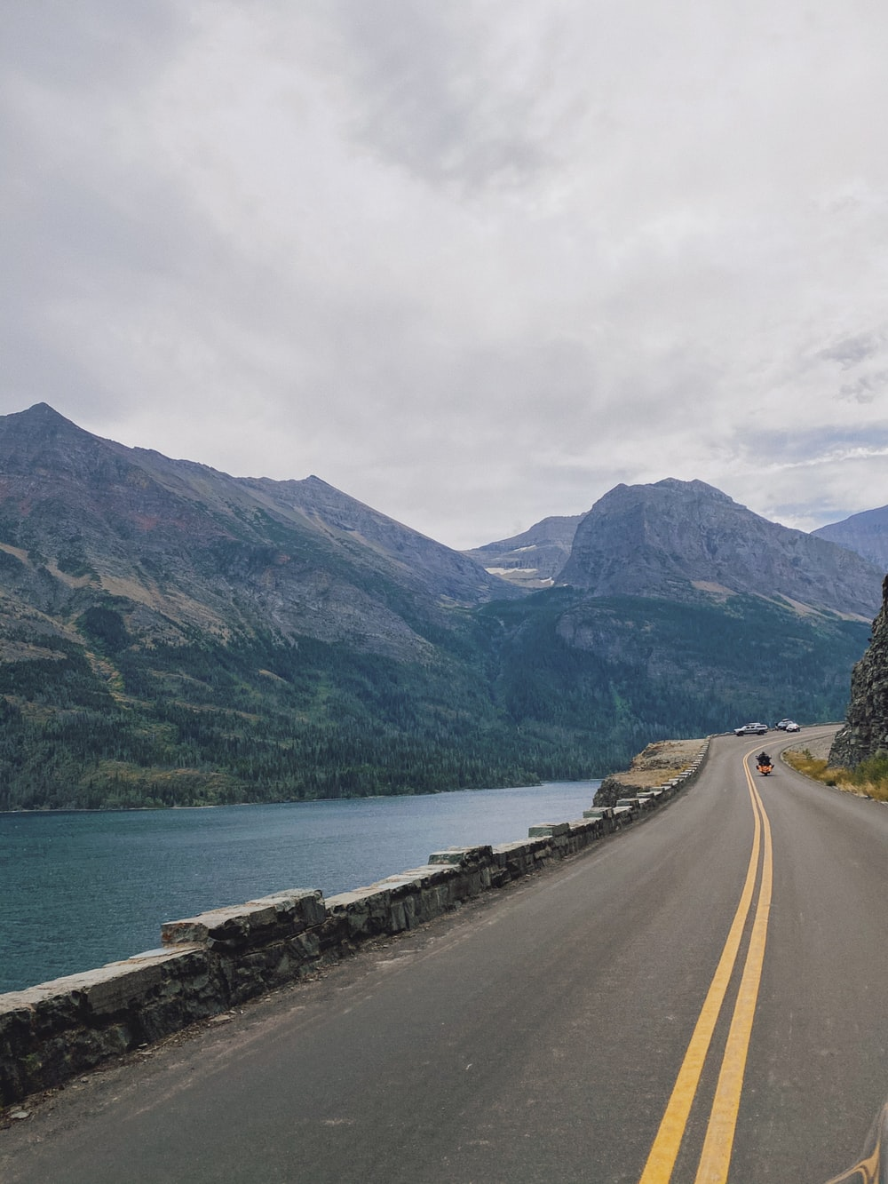 gray concrete road near body of water and mountains during daytime