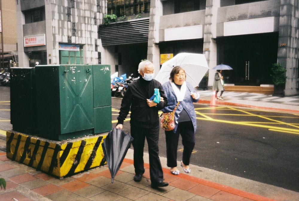 man in blue jacket and black pants standing beside woman in yellow and black jacket