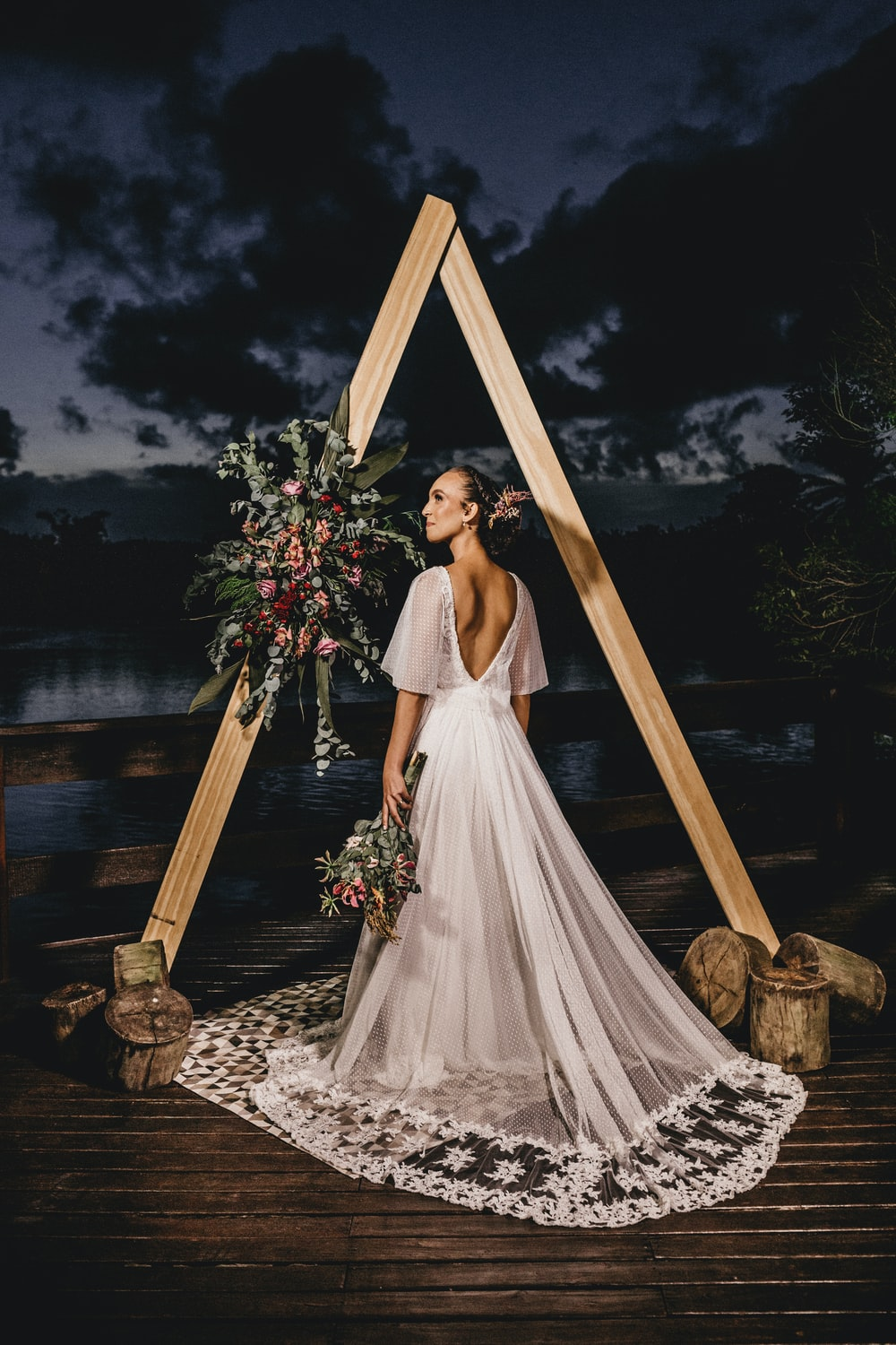 woman in white wedding dress standing on brown wooden ladder