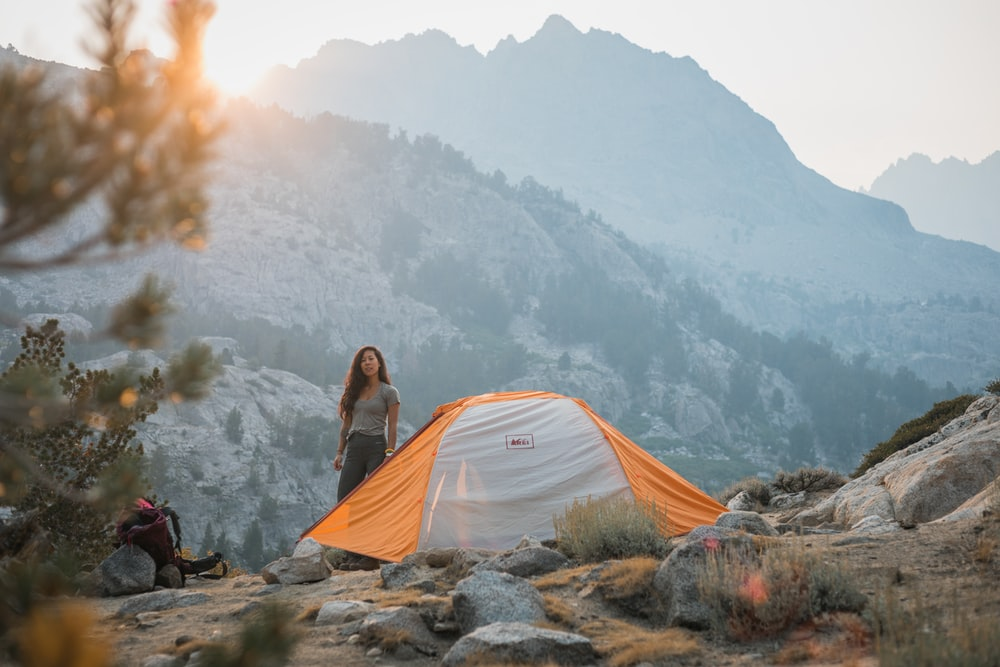 woman in gray jacket sitting on gray tent looking at mountains during daytime