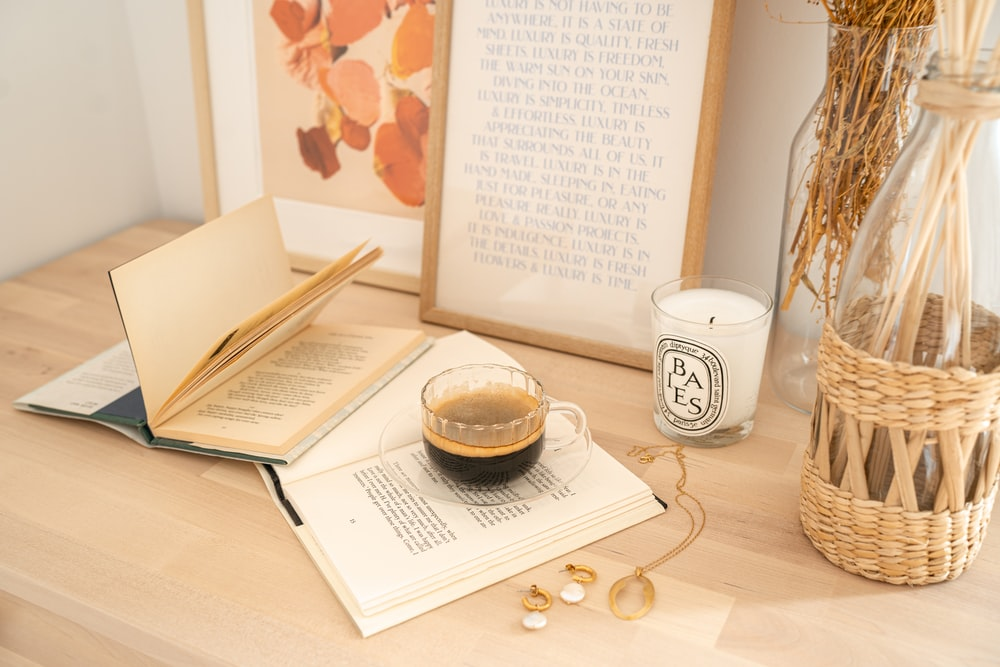 white ceramic mug beside white book on brown wooden table
