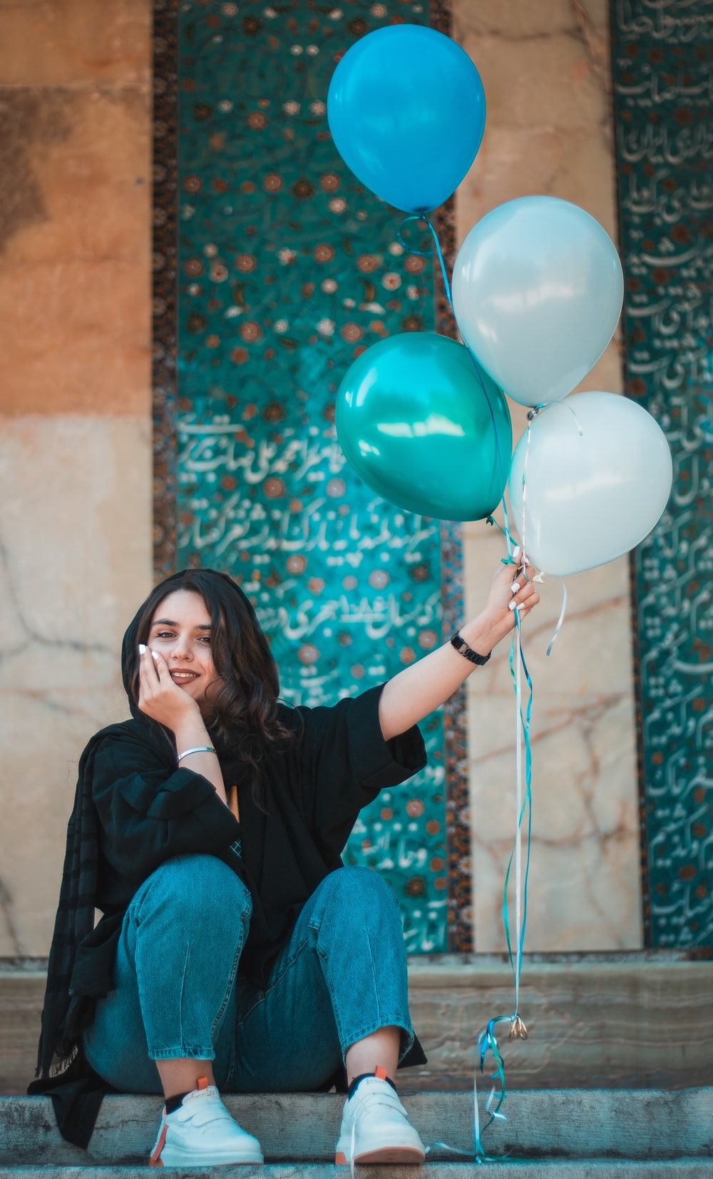 woman in black long sleeve shirt holding blue balloons