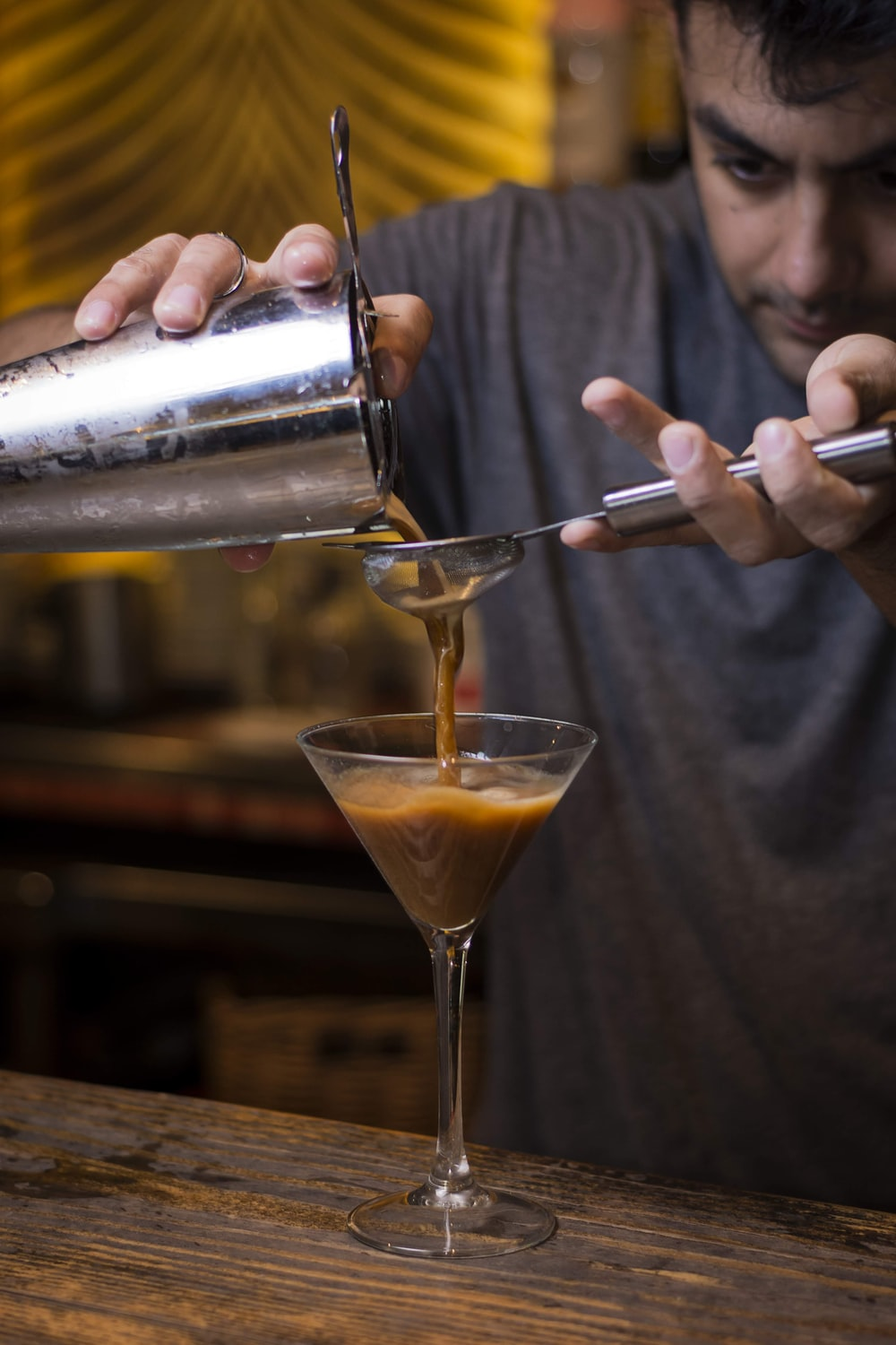 man in gray crew neck shirt holding stainless steel cocktail shaker pouring orange liquid on clear