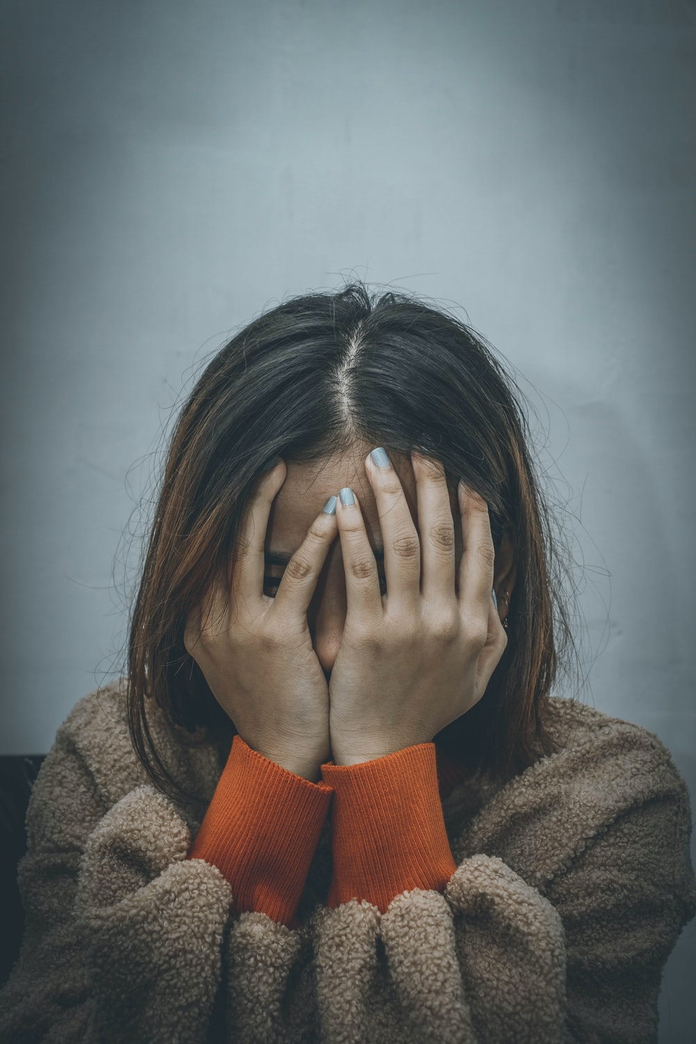 woman in brown sweater covering her face with her hand