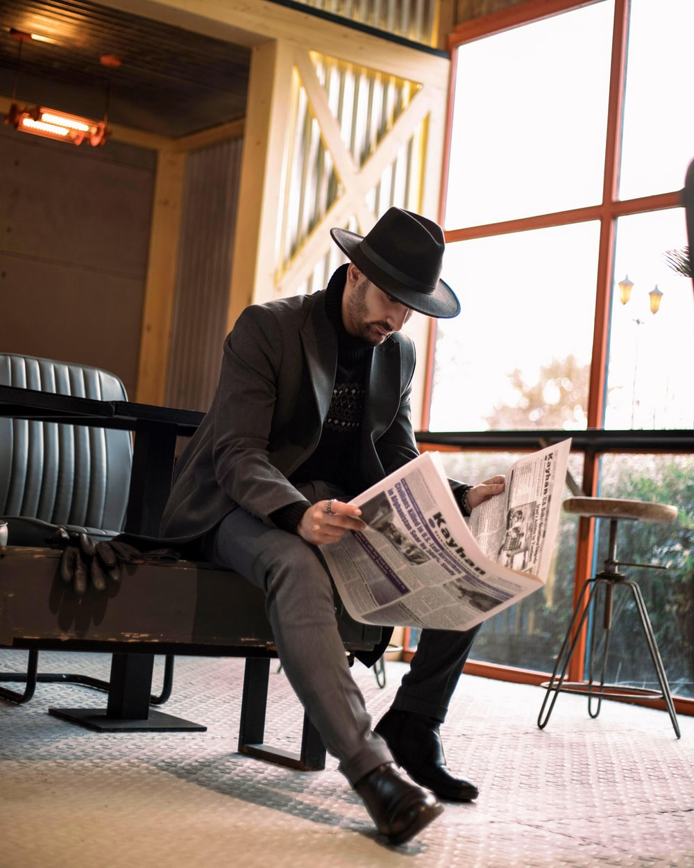 man in black suit jacket and black fedora hat reading newspaper