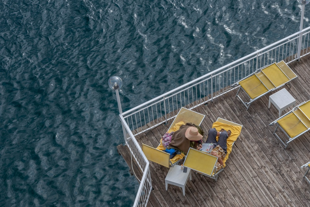 people in yellow shirt sitting on white metal railings during daytime