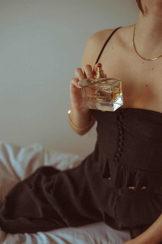 woman in black dress holding clear glass perfume bottle