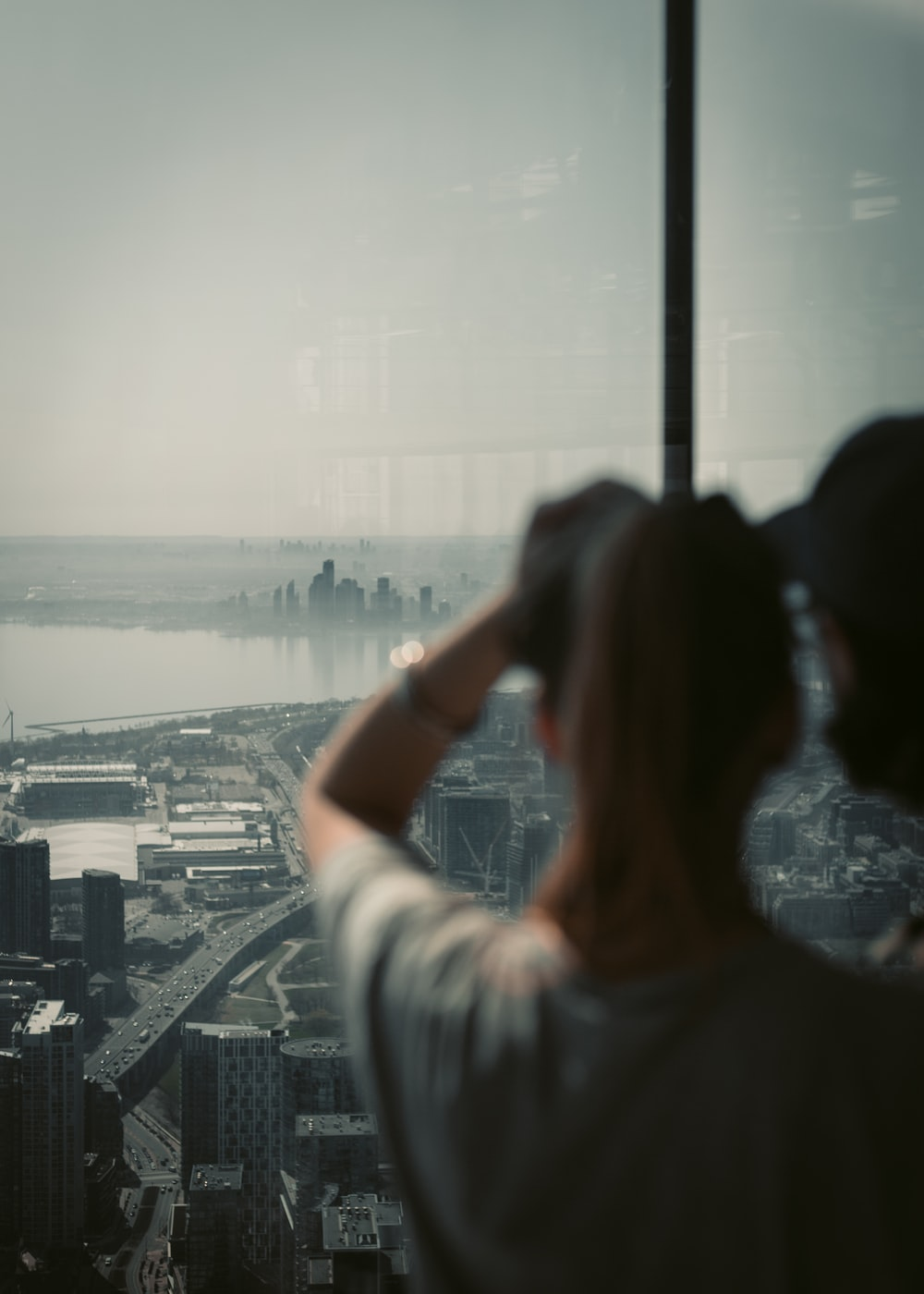 woman in white shirt taking photo of city skyline during daytime