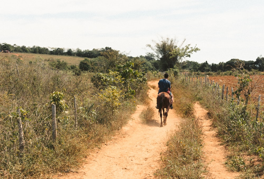 man in red shirt riding on bicycle on dirt road during daytime