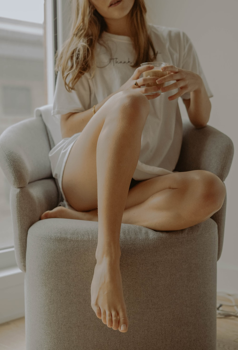 nude woman sitting on gray couch
