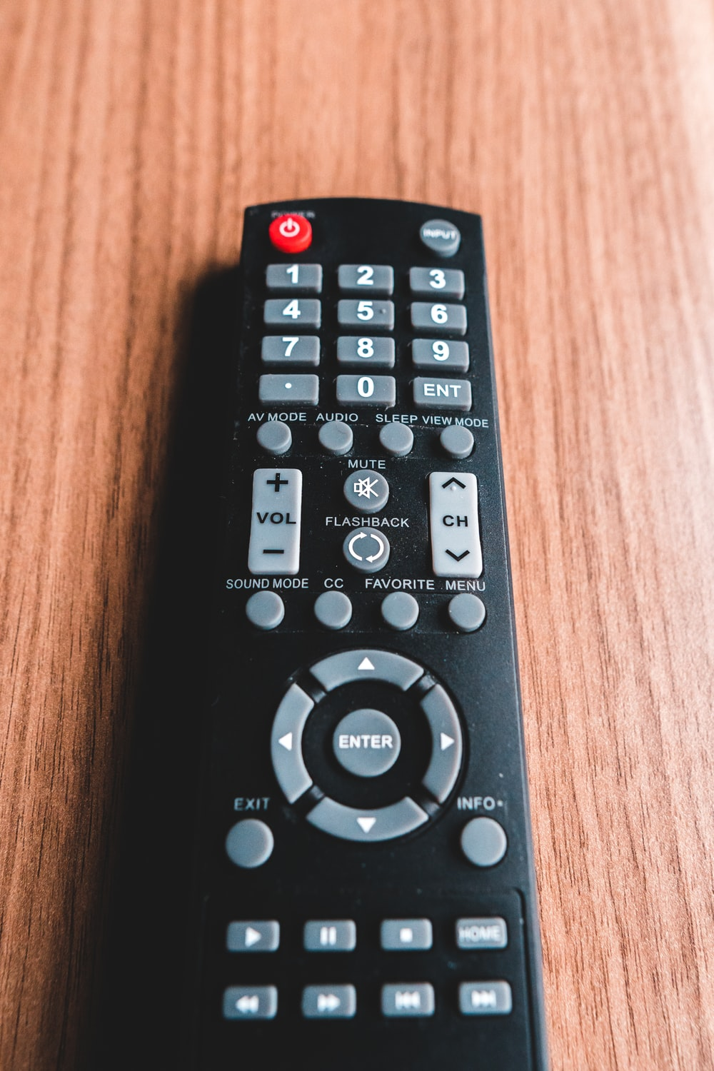 black remote control on brown wooden table