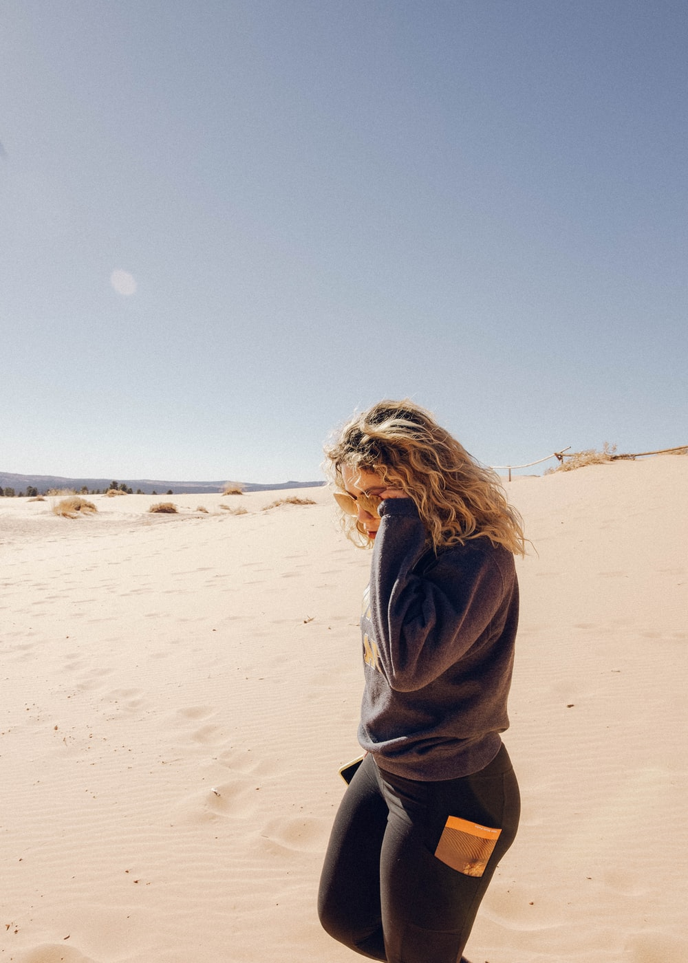 woman in gray hoodie standing on brown sand during daytime