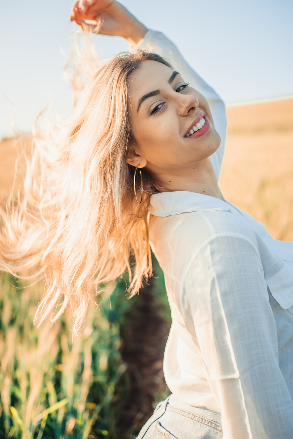 woman in white long sleeve shirt smiling
