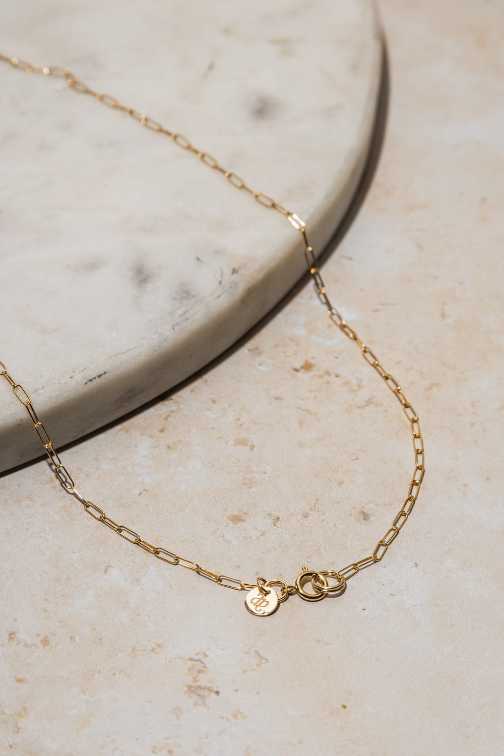 gold necklace on white marble table