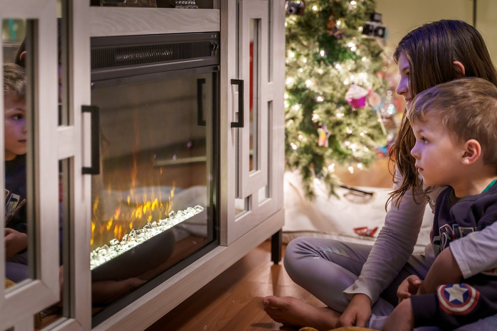 woman in gray long sleeve shirt sitting on floor beside fireplace