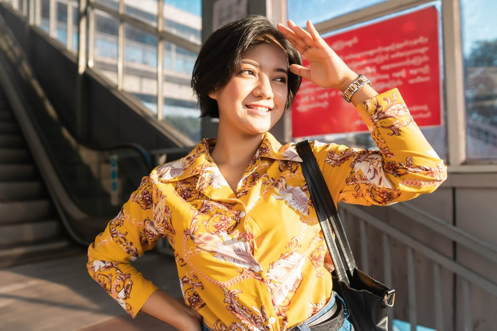 woman in yellow and white floral button up shirt holding her hair