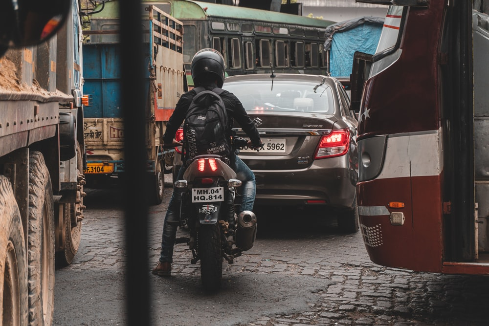 man in black helmet riding black motorcycle on road during daytime