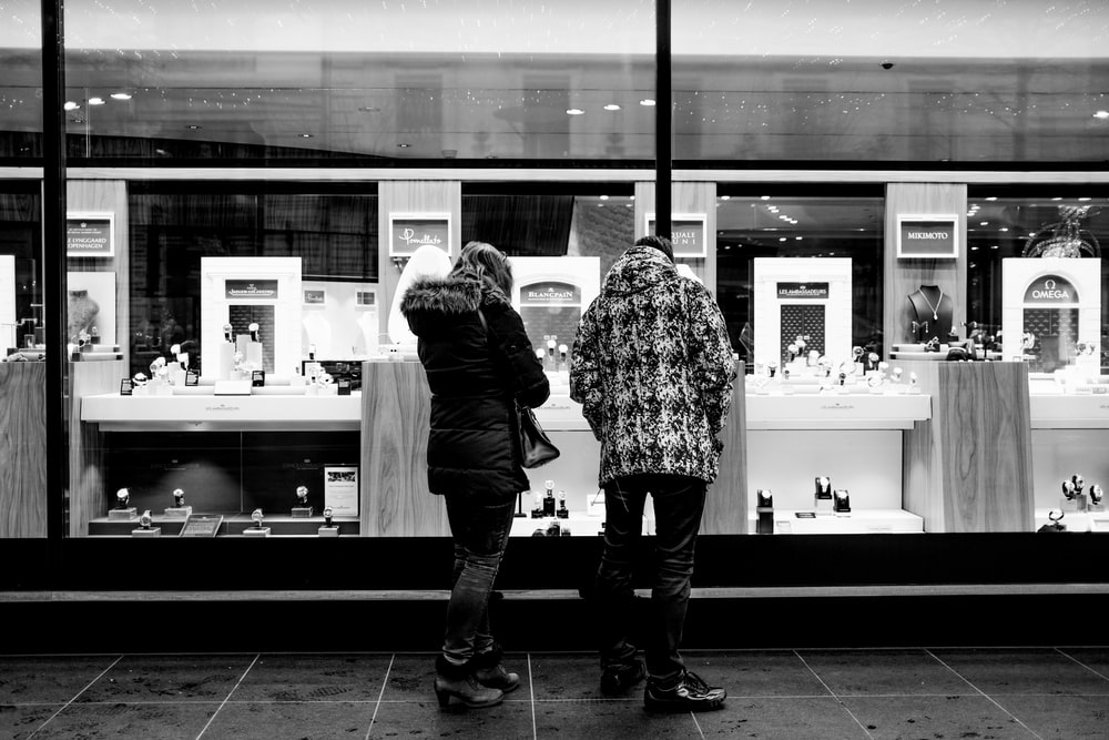 grayscale photo of 2 women standing in front of glass window