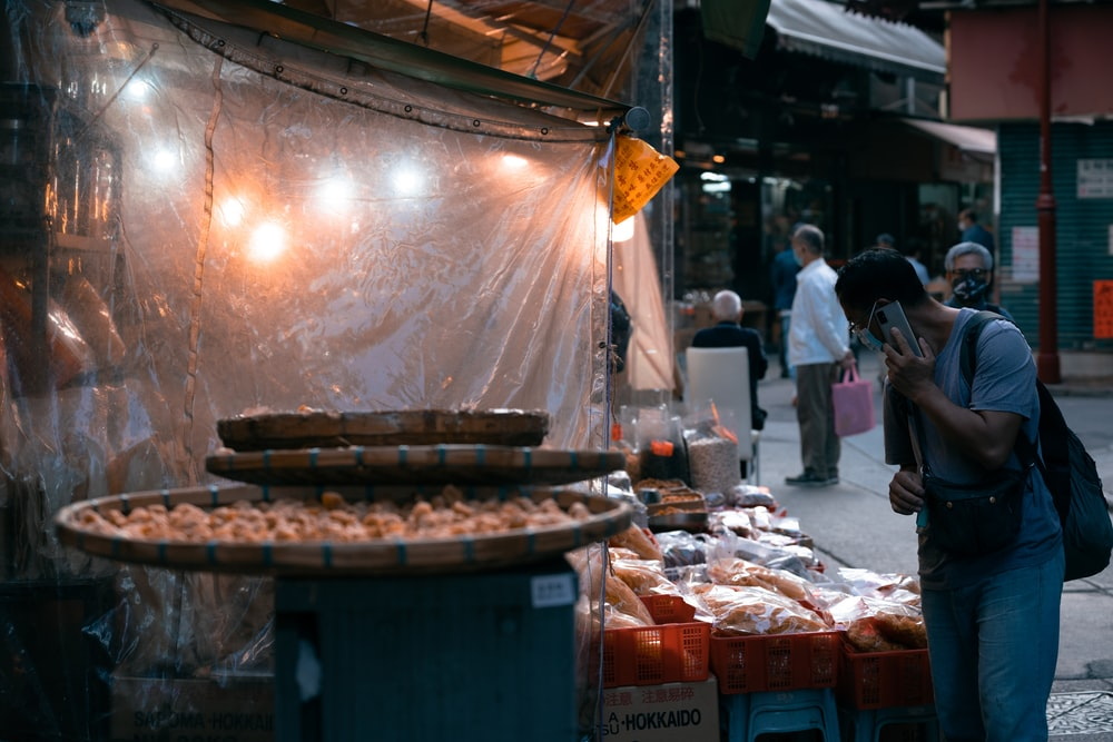 people standing near food stall during daytime