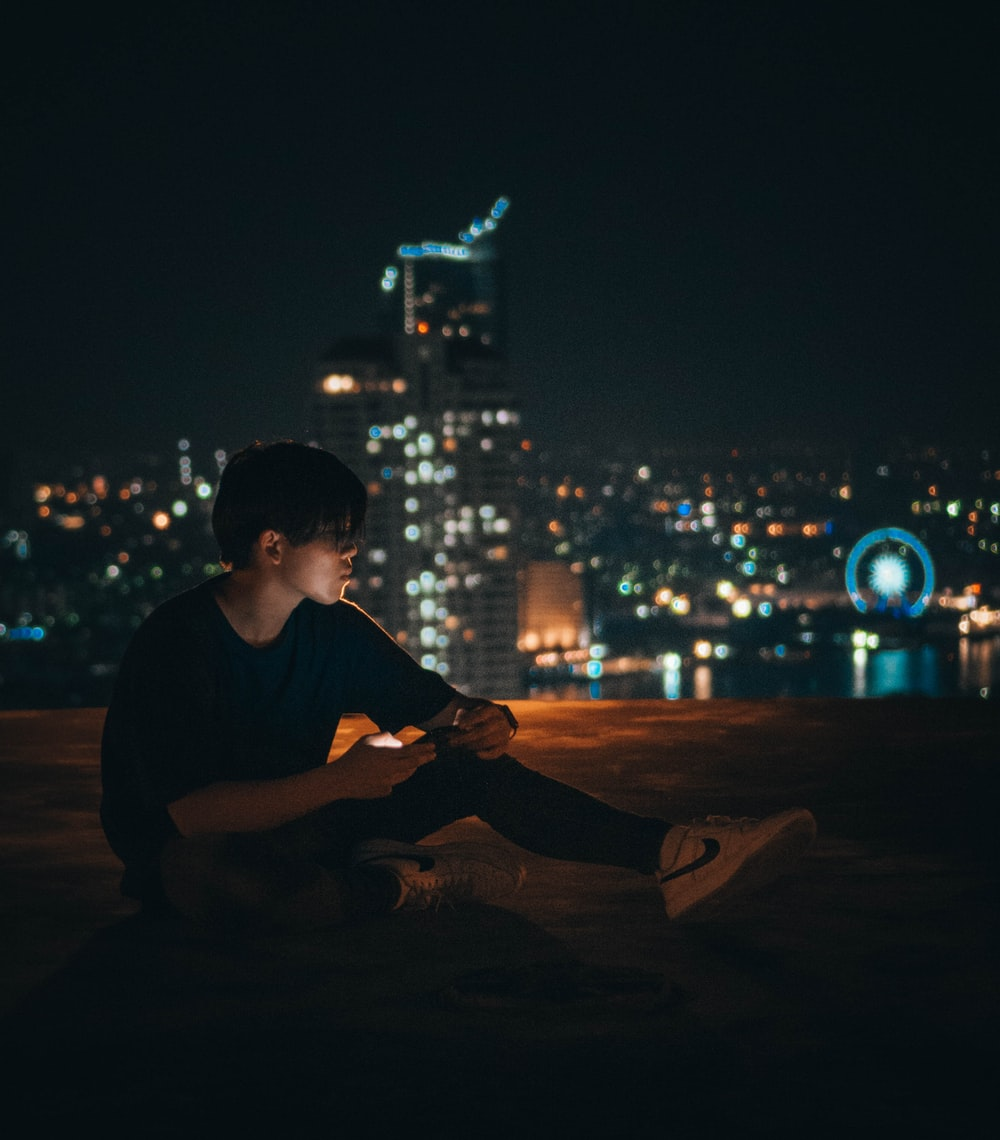man in black crew neck t-shirt sitting on brown wooden table during nighttime