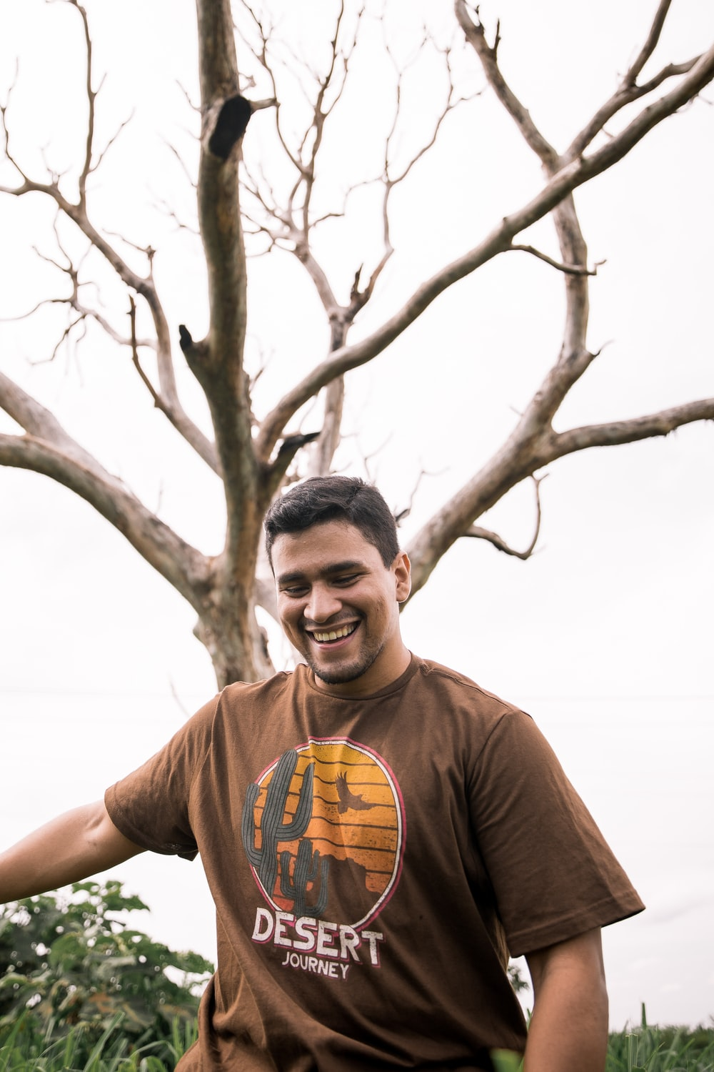 man in brown crew neck t-shirt standing beside bare tree during daytime
