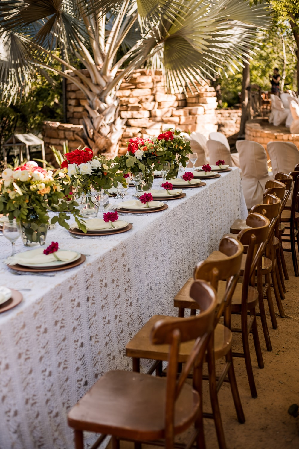brown wooden chairs and table with flowers on top