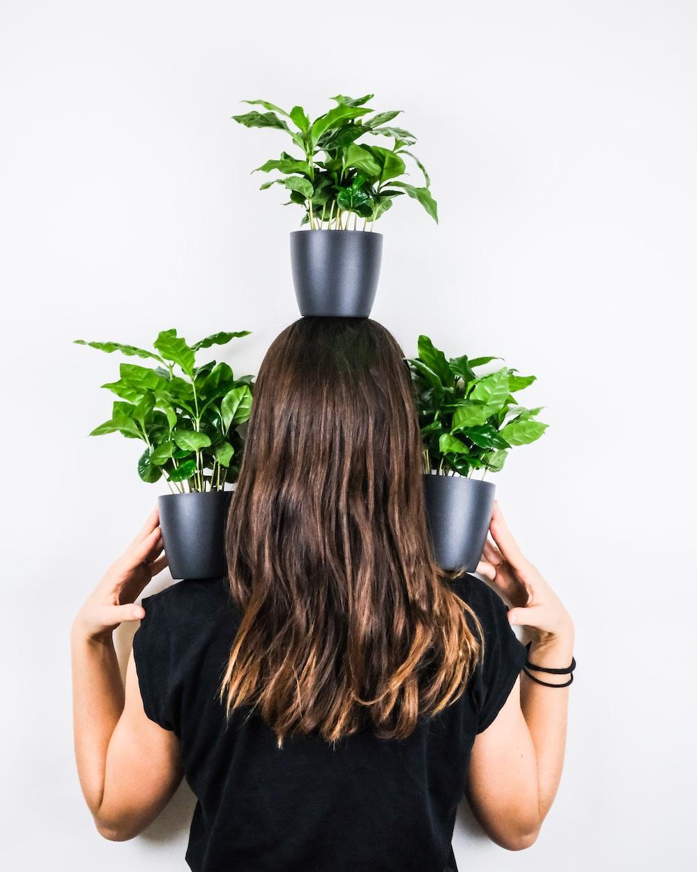 woman in black sleeveless dress holding green plant