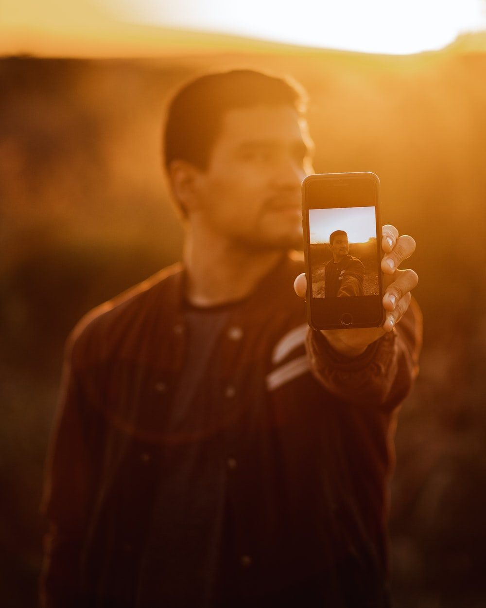 man in black button up shirt holding iphone