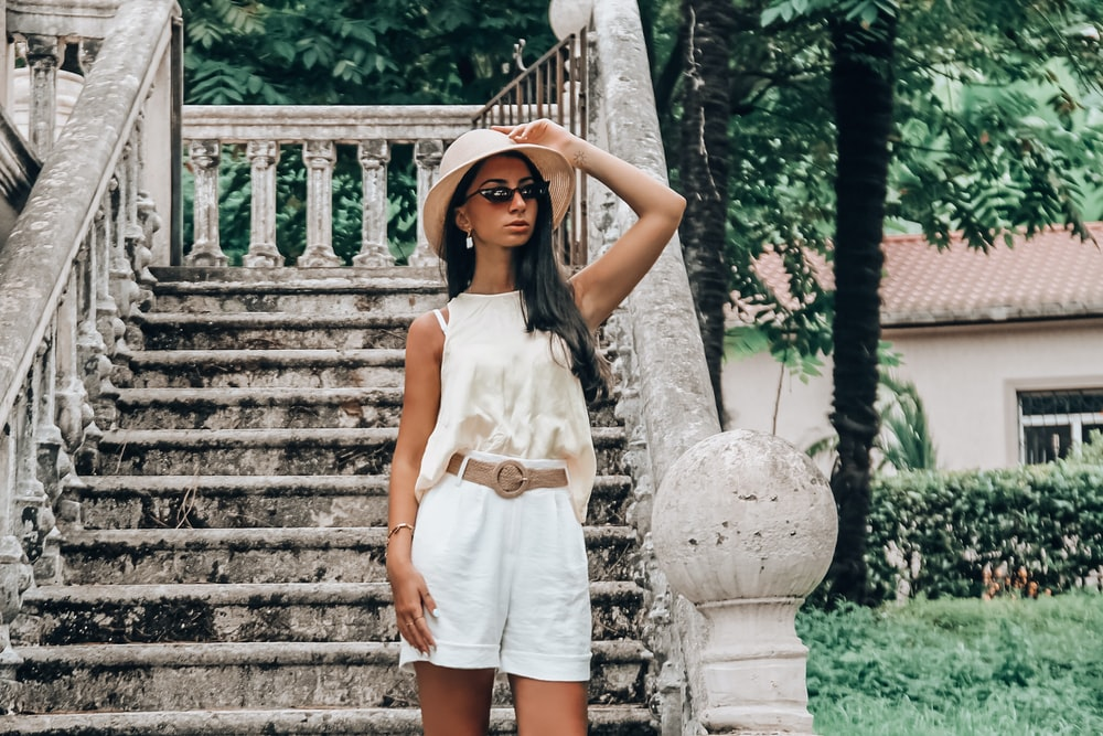 woman in white sleeveless dress standing on stairs