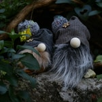 gray and white fur plush toy on brown rock