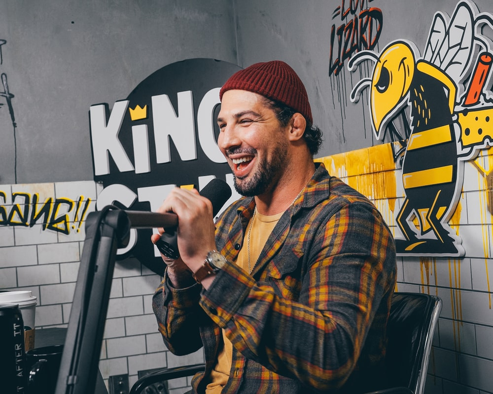 man in red knit cap and yellow and black plaid dress shirt holding microphone