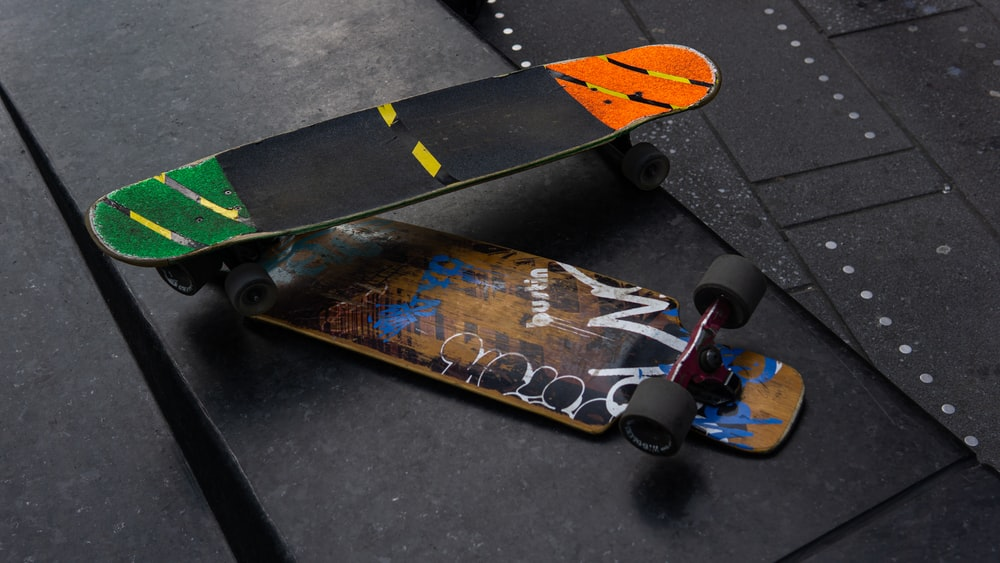 yellow and black skateboard on gray concrete floor