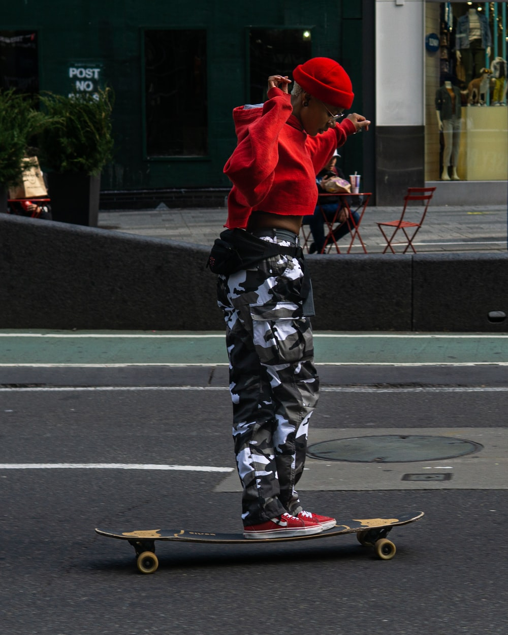 man in red hoodie and black and white camouflage pants standing on red skateboard during daytime