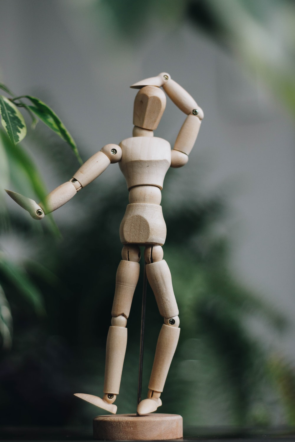brown wooden human figure on green leaves