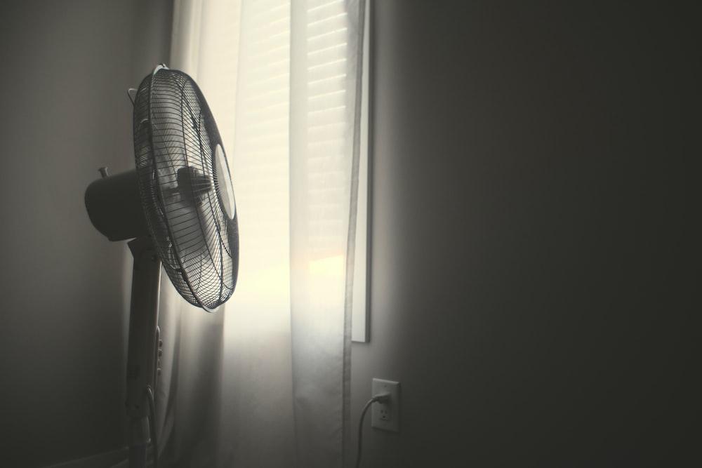 white wall fan turned on near white window blinds