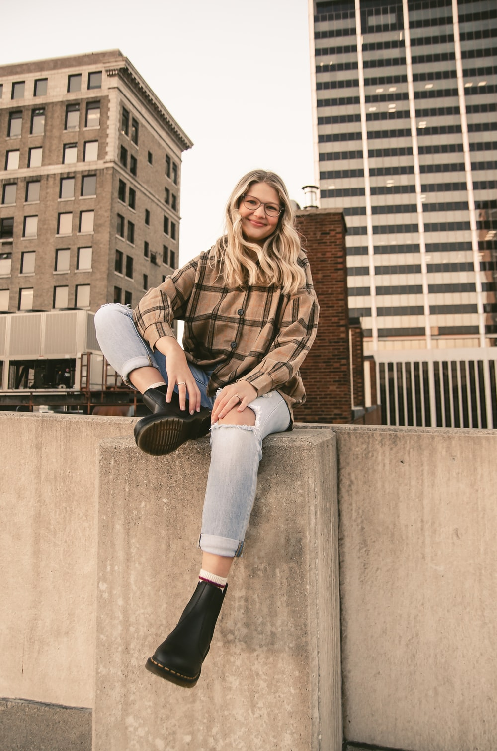 woman in brown leather jacket and blue denim jeans sitting on concrete wall during daytime