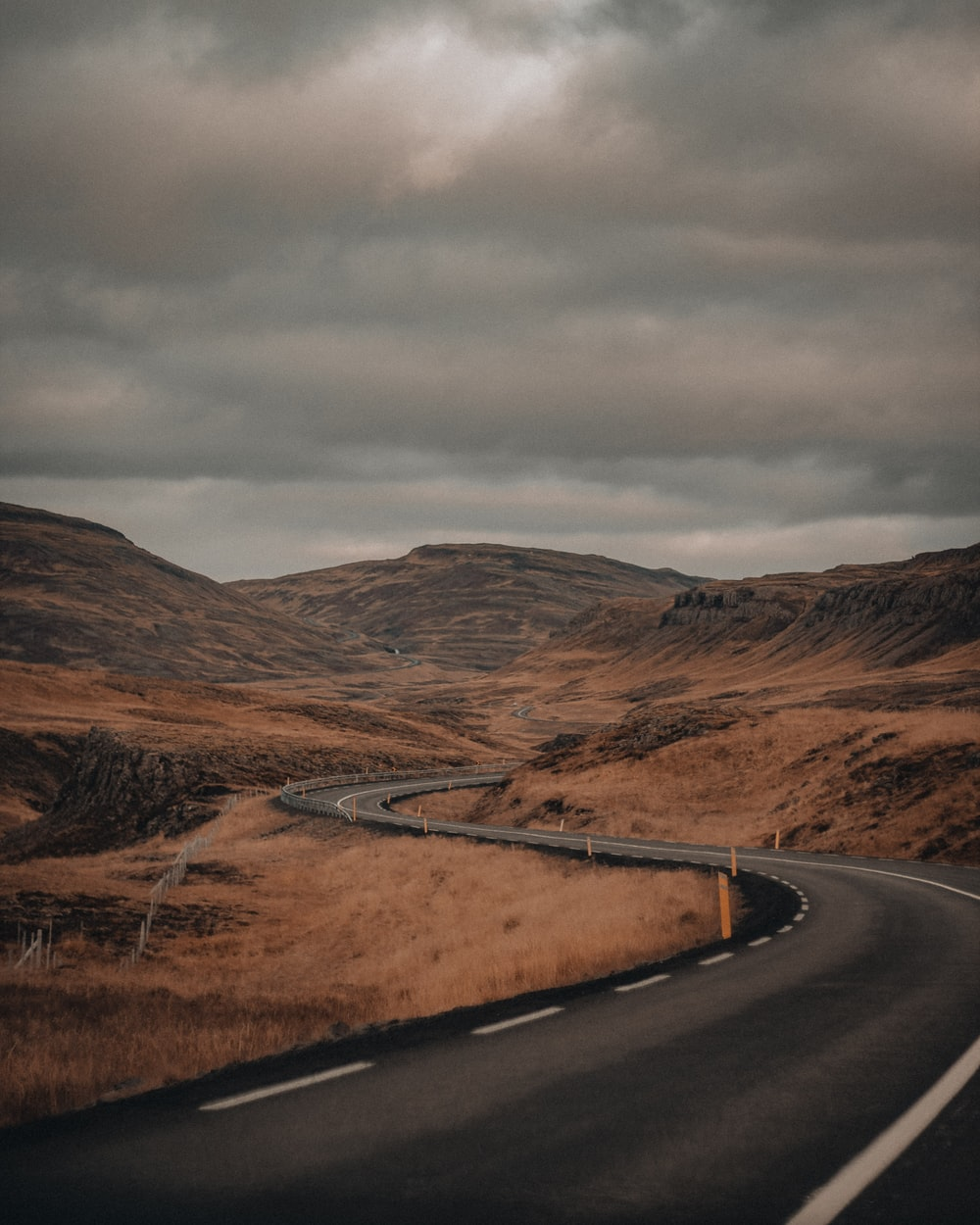 black asphalt road between brown mountains under gray cloudy sky during daytime