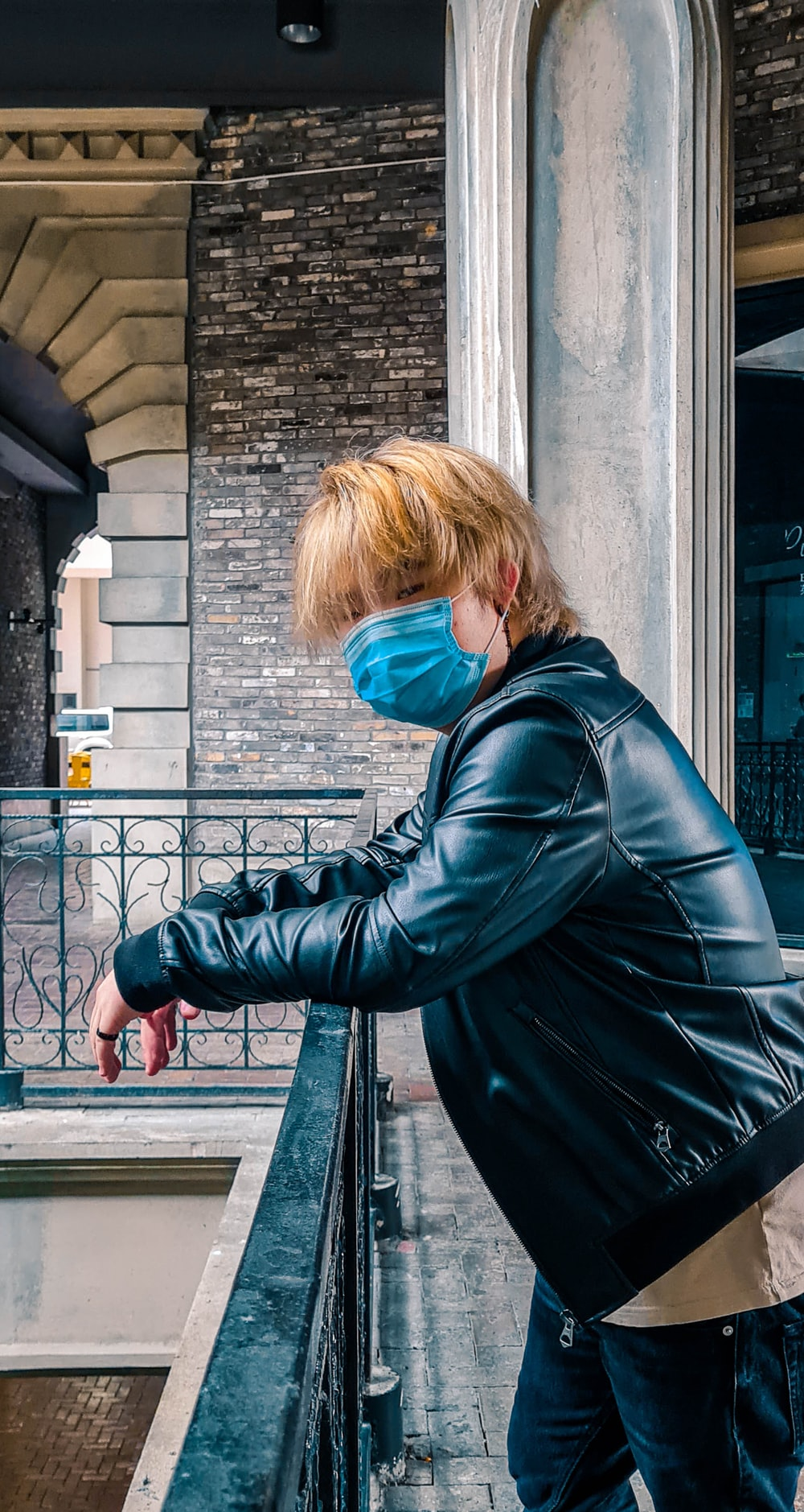 woman in black leather jacket standing beside gray concrete wall during daytime